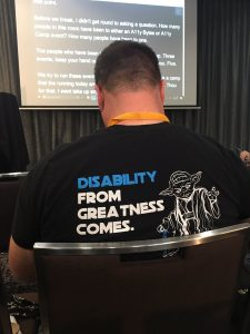 David Masters wearing shirt with image of Yoda and has a quote disability from greatness comes